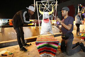 "Darius (left) and Cameron (right) of ""The Amazing Race"" must build the frame of a 'torito,' a paper mache bull rigged with fireworks, hoist it to the top of a 15-foot pole and light it. Competition shows are not usually rigged because of strict federal laws."
