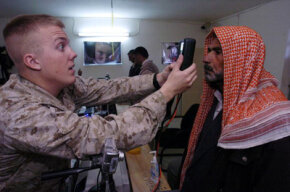 U.S. Marines take the retinal scans and fingerprints of Iraqi residents of Fallujah for their required biometric cards.