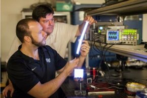 Dr. David Carroll, director of the Center for Nanotechnology and Molecular Materials at Wake Forest University, and graduate student Greg Smith (black shirt) look at FIPEL lighting.