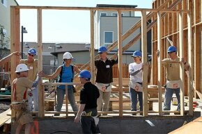 """人类志愿者的栖息地设定了一个墙框架,因为他们帮助加利福尼亚州奥克兰建造一个家。他们是五天闪电图的一部分,框架10个房屋,有数百名志愿者。""""border="""