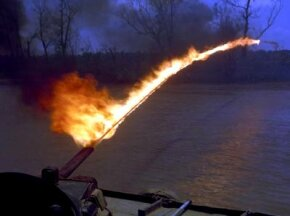 "A U.S. Navy ""Zippo"" flamethrower is tested from a patrol boat. The unreliability of electronic ignition systems meant that operators sometimes had to use a Zippo lighter to ignite the fuel as it left the nozzle."