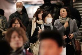 Commuters in Tokyo wear surgical masks to help protect themselves from an influenza outbreak.