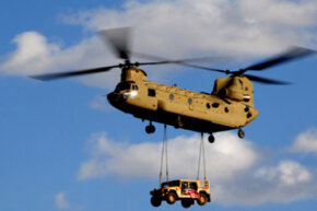 A U.S. Army CH-47 Chinook helicopter transports a Humvee.