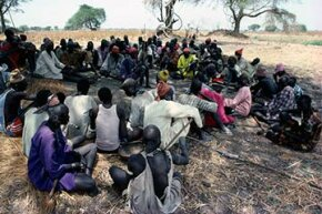 Guests at Dinka wedding in Sudan listen to a traditional story teller.