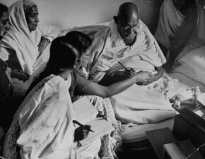 Indian leader Mohandas K. Gandhi, sitting on a mattress on the floor, surrounded by people at the end of his last fast.