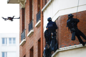 A French police intervention unit takes position outside a Paris apartment while a drone flies outside windows.
