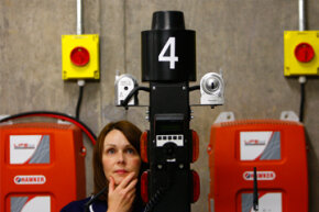 Nurse Lesley Shepherd poses next to a robot tested for use at the Forth Valley hospital in Larbert, Scotland, on June 18, 2010. The robots were deployed in the hospital for tasks such as transporting clinical waste, dirty linen and food.