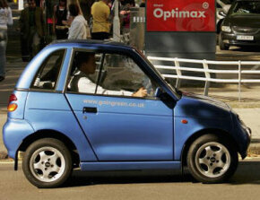England's most popular electric car, the G-Wiz, drives past a petrol station in London. Are its energy-saving qualities too good to be true? See more pictures of small cars.