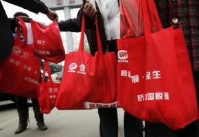 Chinese shoppers carry reusable bags because the government has announced a nationwide ban on free plastic bags in an effort to reduce crude oil consumption. Environmental initiatives are one example of a real-life public goods game.