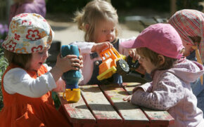 German toddlers play in the garden at the Spreekita kindergarten in Berlin. Kindergarteners' behavior best exemplifies game theory's economic model.
