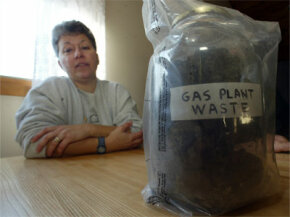 "A Tiverton, R.I., resident poses next to a container labeled ""Gas Plant Waste"" in 2005. The state believes the area contamination was caused by the Fall River Gas Co. dumping coal gasification waste for decades."