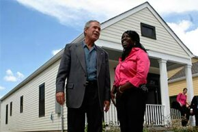 Former U.S. President George W. Bush speaks with new homeowner Joanika Davis at a mixed housing development in New Orleans. Developers of low income housing can get business tax credits.