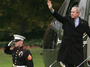 Former U.S. President George W. Bush (right) waves on the steps of the Marine One before his departure from the White House Nov. 19, 2007, in Washington, D.C. Watch Stuff You Should Know on presidential perks.