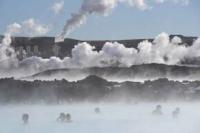 Visitors soothe themselves in a geothermal spa in Grindavik, Iceland while, in the distance, a power plant transforms the rising steam into electrical power.