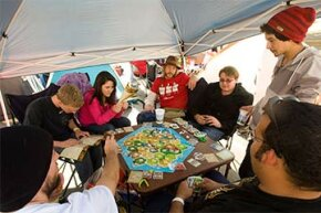 """A group of campers play """"Settlers of Catan"""" as they wait for a grand opening of a Chick-Fil-A in California in 2011."""