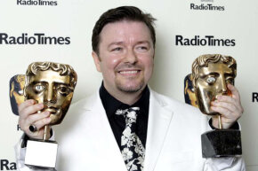 "Actor and writer Ricky Gervais poses holding two awards for ""The Office"" at the British Academy Television Awards in 2003."