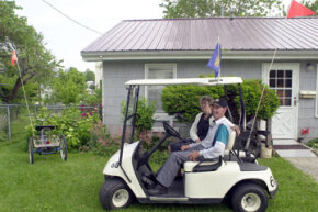 Gary Knight, 48, sits in his golf cart with his mother, Joann Hall, at their home in Sweet Springs, Mo. For the last six years Knight, who has cerebral palsy, has used a golf cart as a way to get around in the small town.