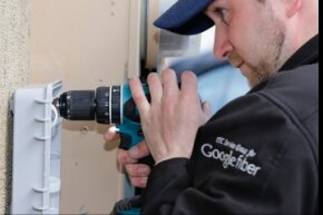 A Google Fiber technician installing a fiber optic box at a residential home.