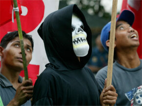 Protesters often don a Grim Reaper costume to make a point. This one is demonstrating against the presence of the International Monetary Fund and the World Bank during a rally in the Philippines in October 2004.