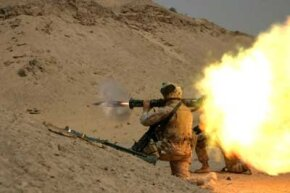 Soldier fires a handheld rocket launcher in training