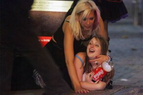 Two girls lie on the pavement in Bristol City Centre, England after a night of binge drinking.