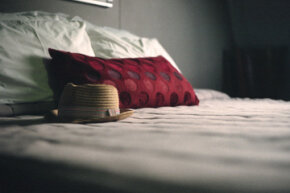 While putting your hat down on a bed might not conjure up evil spirits, it may transfer head lice.