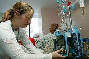 Nurse Autumn Small adjusts an IV drip machine for a patient receiving treatment for a rare form of cancer at a children's hospital in San Francisco, 2005. Health care costs a lot more in the U.S. than in other developed countries.