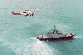 A Hong Kong harbor helicopter flies low over a police boat in China. Flying a helicopter over water is often much more dangerous than it looks; rough weather could make a shoot downright deadly. See more TV show pictures.