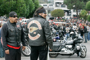 A pair of Hells Angels members look on as crowds jam a funeral home parking lot during the memorial for the Hells Angels San Francisco chapter leader in Daly City, Calif., on Sept. 15, 2008.