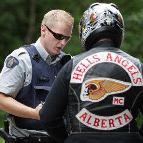 An RCMP officer stops an Alberta member of the Hells Angels motorcycle gang at a roadblock after he left the White Rock chapter's property in Langley, British Columbia, on July 26, 2008.