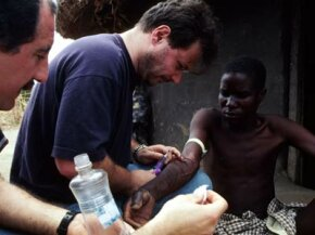 AIDS researcher Dr. Giuliano Rizzardini takes a blood sample from an AIDS patient with Karposi's sarcoma at a village outside Gulu, Uganda.