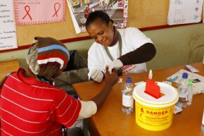 A woman administers an AIDS test at a South African clinic.