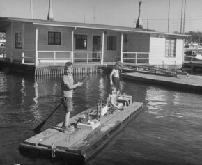 Near a wooden houseboat, children play on their own, much tinier houseboat. Both would need maintenance.