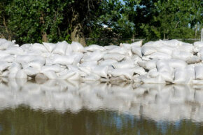 Sandbags holding back a mass of floodwaters. See more pictures of natural disasters.