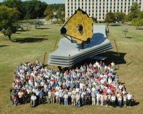 A model of the James Webb Space Telescope on the lawn at Goddard Space Center. You can gauge the size of the telescope by comparing it with the design team standing in front of it.