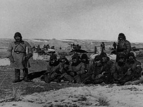 Japanese soldiers stand guard over eight Chinese prisoners in Mongolia during the Imperial Army's 1941 Winter Hygienic Research program.