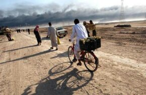 A man carries produce on his bicycle near the entrance to the besieged city of Basra, Iraq as civilians flee due to the war.