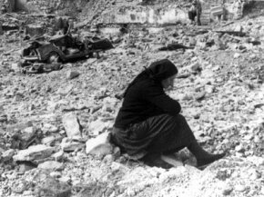 A woman sits amid the rubble of what was once the village of Longarone, below the Vaiont Dam in Italy.