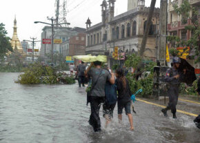 People walk in a flooded street in Myanmar's largest city, Yangon, on May 3, 2008, after a hurricane (although it's called a cyclone there).