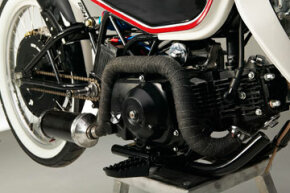 The gas engine is mounted low by the pedals, helping center the bike's weight distribution.