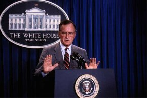 President George H.W. Bush speaks at a press conference in 1990. Conspiracy theorists thought his 'new world order' speech foretold a one-world government.