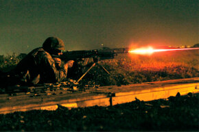 Cpl. Robert Giuliani, a Combat Logistics Company 36 Marine, fires tracer rounds from a 240G medium machine gun during the night fire portion of Exercise Dragon Fire 2009.