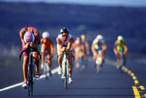 Cyclists make their way along the desolate lava fields at Kona. See more Olympic game pictures.
