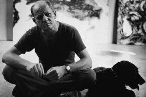 Pollock sits with a dog at his Springs studio in New York in 1953.