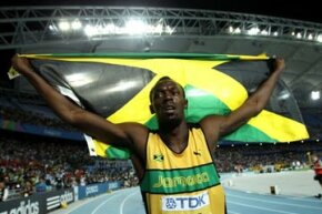 """Sprinter Usain Bolt waves the Jamaican flag after winning the gold medal in the 200 meters at the IAAF World Championships in September 2011.  Bolt, who holds the world records in the 100 and 200 meters, is considered """"the fastest man alive."""""""