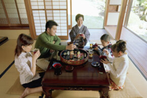 A Japanese family at dinner in their traditional wood and paper house.