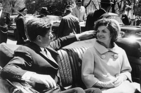 In happier times, JFK fixes Jackie's windblown hair on a ride between the White House and Blair House in 1961.