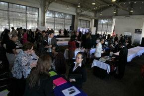Job seekers speak to recruiters at a San Francisco, Calif., job fair.