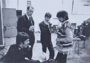 "Producer George Martin keeps his eyes on the camera, while ""the boys"" listen to Paul's run-through of a bass part during the Sgt. Pepper sessions."