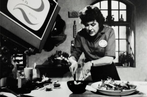 A 1960s-era photo of Julia Child taping an episode of her TV show in her home kitchen.